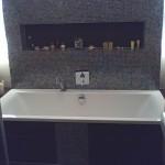 Gefliestes Badezimmer mit Glasmosaik