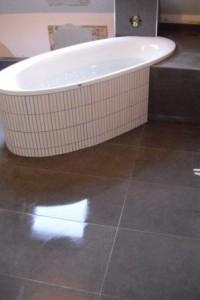 Ovale Badewanne mit Fliesenstreifen verlegt